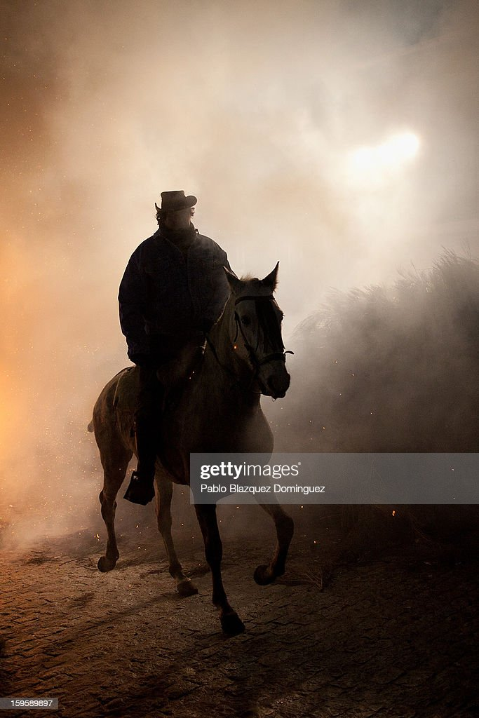 A man rides a horse through smoke on January 16, 2013 in San Bartolome de Pinares, Spain. In honor of San Anton, the patron saint of animals, horses are riden through the bonfires on the night before the official day of honoring animals in Spain.