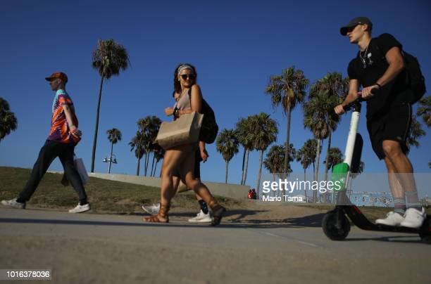 A man rides a Lime shared dockless electric scooter along Venice Beach on August 13 2018 in Los Angeles California Shared escooter startups Bird and...