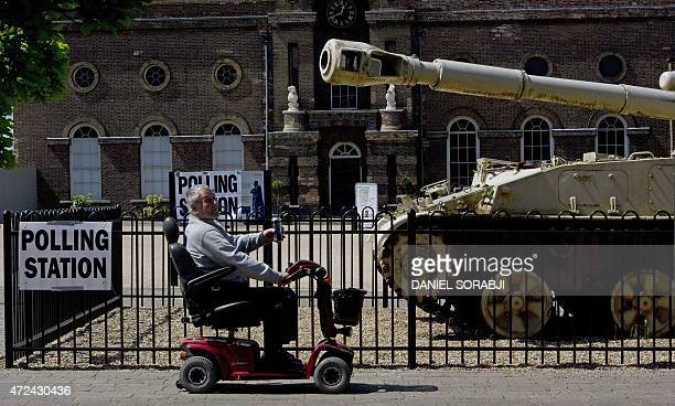 A man rides a mobility scooter past a 2S3 M1973 Akatsiya 152mm selfpropelled gun howitzer outside the Greenwich Heritage Centre set up as a polling...