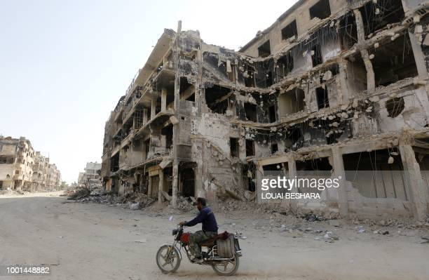 A man rides a motorbike by destroyed buildings in Harasta on the outskirt of the Syrian capital Damascus on July 15 2018 After a blistering weekslong...