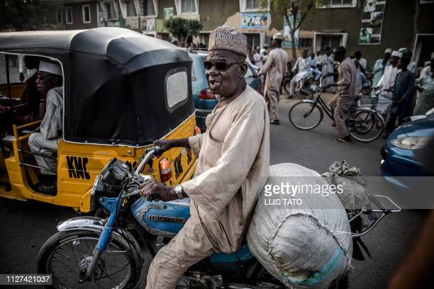 Man rides a motorbike in a traffic jam created by All Progressives Congress Party supporters celebrating initial results released by the Nigerian...