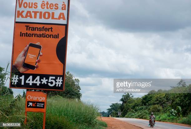 A man rides a motorbike next to a road sign reading 'you are in Katiola' at the entrance of the city of Katiola on September 6 2017 where nearly 100...