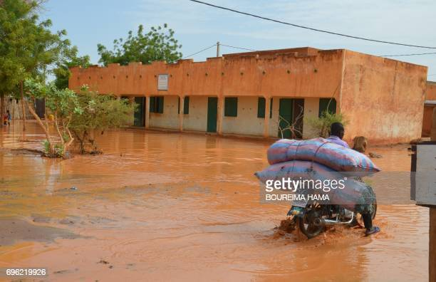 A man rides a motorbike with his belongings in a flooded street of Niamey following heavy rains on June 15 2017 At least nine children have been...