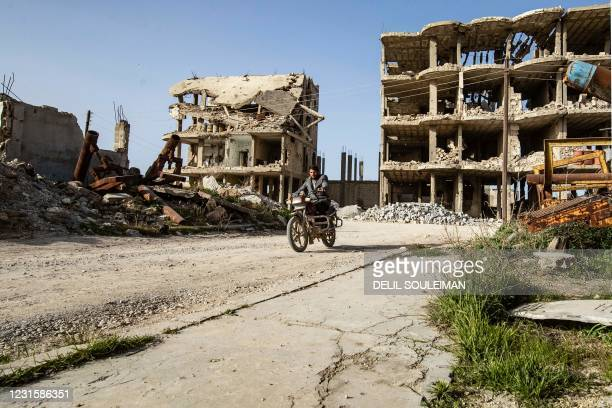 Man rides a motorcycle amid destroyed buildings in the Syrian Kurdish town of Kobane, also known as Ain al-Arab, in the north of Aleppo governorate...