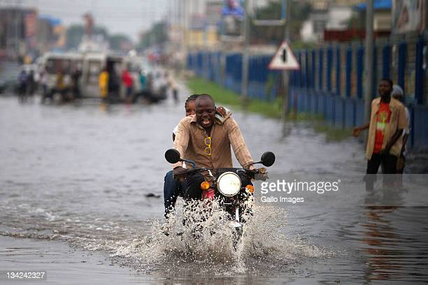 A man rides a motorcycle carrying a passenger through floodwater after a heavy rain storm delayed voters on November 28 2011 in Kinshasa Democratic...