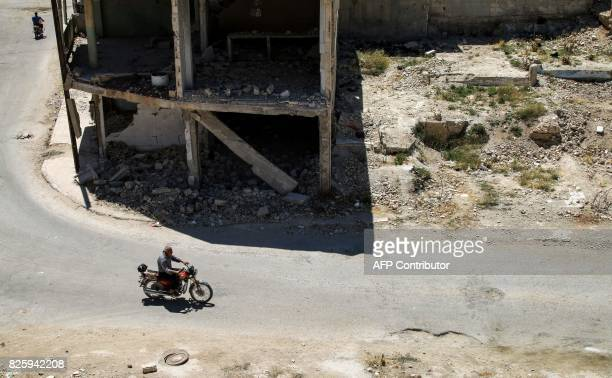 A man rides a motorcycle down a street past a damaged building in the central Syrian rebelheld town of Talbiseh north of Homs on August 3 2017 A...