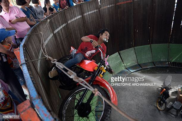 A man rides a motorcycle in a cylinder to entertain visitors during the annual buffalo races in Chonburi southeast of Bangkok on October 7 2014...