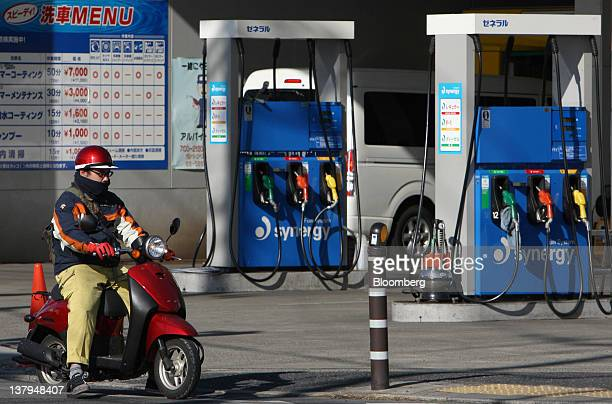 A man rides a motorcycle in front of a TonenGeneral Sekiyu KK gas station in Tokyo Japan on Monday Jan 30 2012 TonenGeneral Sekiyu KK agreed to buy...