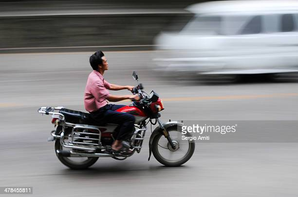 CONTENT] A man rides a motorcycle in Zunyi China