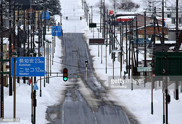 A man rides a motorcycle on a road in Kutchan Hokkaido Japan on Saturday Feb 14 2015 Japan had a record number of foreign visitors in 2014 attracted...