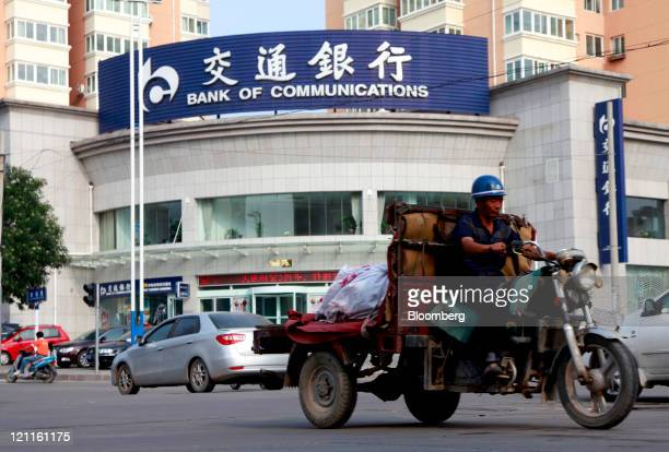 A man rides a motorcycle past a Bank of Communications Co Ltd branch in Yulin Shaanxi Province China on Saturday Aug 13 2011 Bank of Communications...
