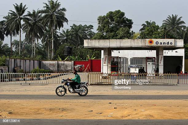 A man rides a motorcycle past a closed Oando Plc gas station in Port Harcourt Nigeria on Thursday Jan 14 2016 With his security forces engaged in...