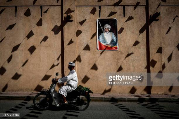 A man rides a motorcycle past a wall of the Nizwa fort bearing a portrait of the Omani Sultan before the first stage of the 2018 cycling Tour of Oman...
