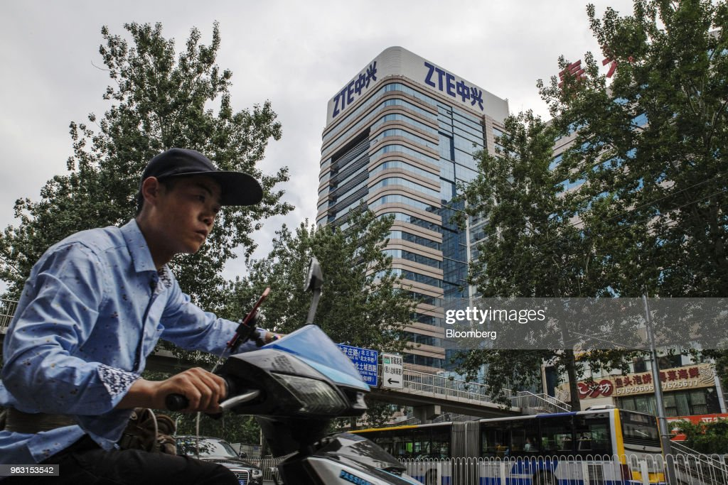 A man rides a motorcycle past a ZTE Corp. building in Beijing, China, on Thursday, May 24, 2018. PresidentDonald Trumpsaid the U.S. would allow Chinese telecommunications-equipment maker ZTE Corp. to remain in business after paying a $1.3 billion fine, changing its management and board and providing 'high-level security guarantees.' Photographer: Gilles Sabrie/Bloomberg via Getty Images