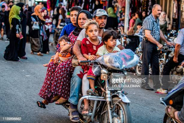 Man rides a motorcycle with a woman and children through a street market in the predominantly-Kurdish northeastern Syrian city of Qamishli on August...