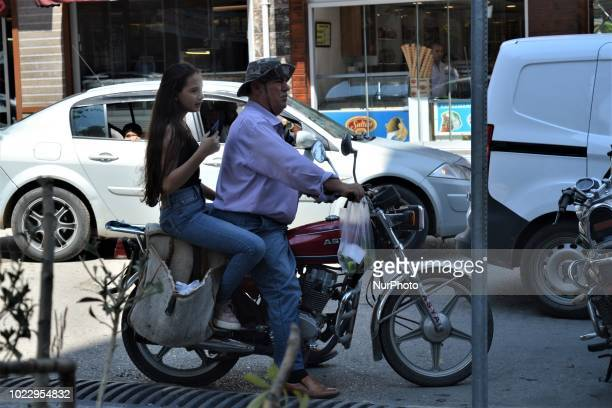 A man rides a motorcycle with a woman on a road on the last day of Eid alAdha in southern Hatay province of Turkey on August 24 2018 Hatay is...