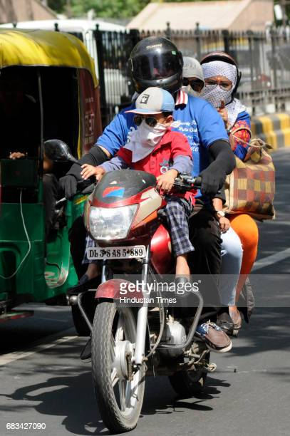 A man rides a motorcycle with his family on a hot summer day on May 15 2017 in New Delhi India Heat wave conditions prevailed in the capital as...