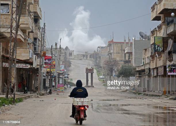 A man rides a scooter on a street during reported air strikes in the town of Khan Sheikhun in the southern countryside of the rebelheld Idlib...