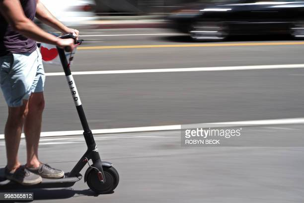 A man rides a shared electric scooter in Santa Monica California on July 13 2018 Cities across the US are grappling with the growing trend of...