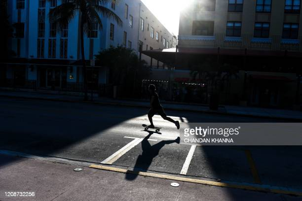 Man rides a skate board on a deserted ocean drive amid fears over the spread of the novel coronavirus in South Beach in Miami, on March 31, 2020. -...