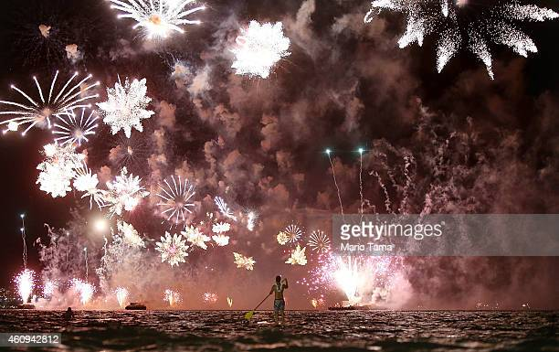 A man rides a stand up paddle board as fireworks explode above him during New Year's festivities on Copacabana Beach on January 1 2015 in Rio de...
