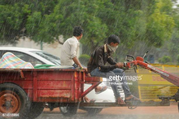 A man rides a tractor amid heavy downpour near India Gate on April 28 2017 in New Delhi India