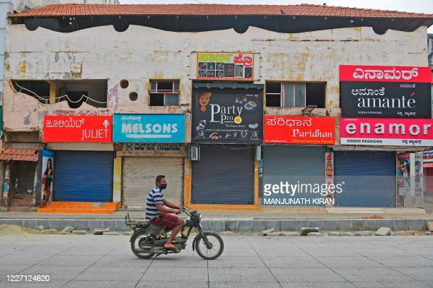 A man rides a twowheeler in front of closed shops in a commercial area during a weeklong lockdown to contain the surge of COVID19 coronavirus cases...
