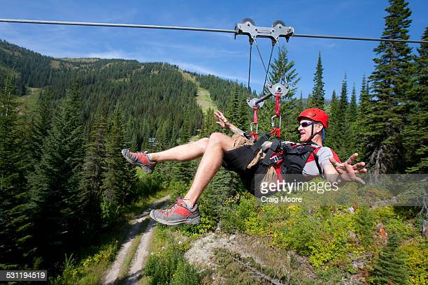 A man rides a zip line in Whitefish, Montana.