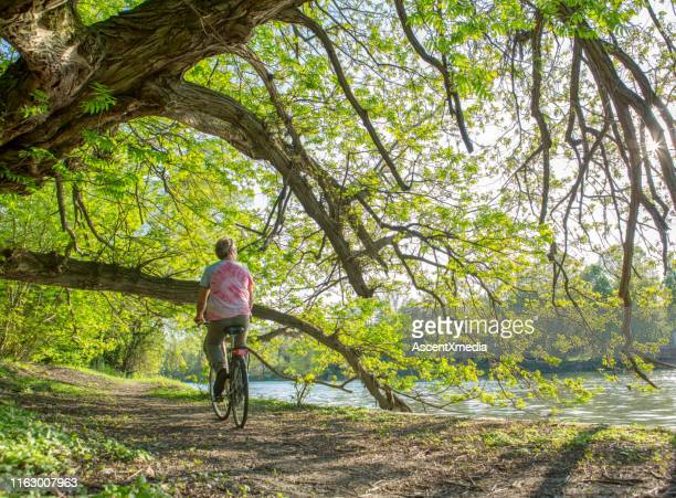man rides along the river on a bicycle - riverbank stock pictures, royalty-free photos & images