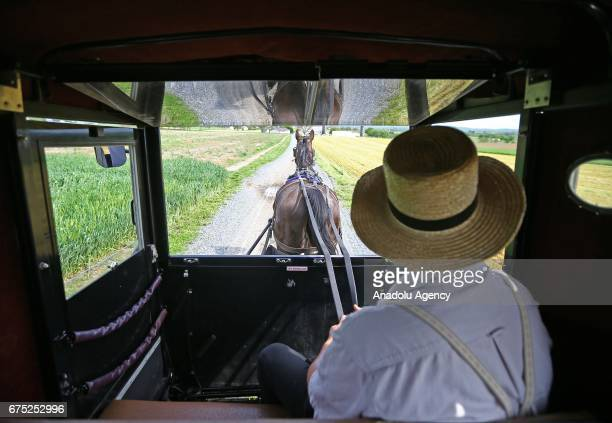 A man rides an Amish horse in a buggy in Central Pennsylvania United States on April 30 2017 Central Pennsylvania is home to an iconic set of plain...