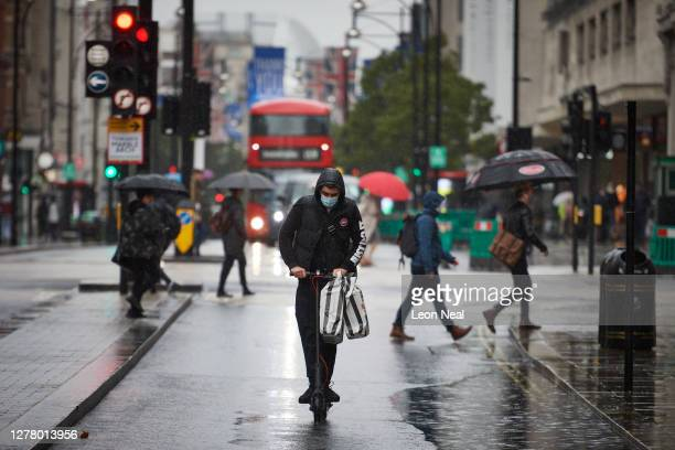 Man rides an escooter on Oxford Street during heavy rain on October 02, 2020 in London, England.