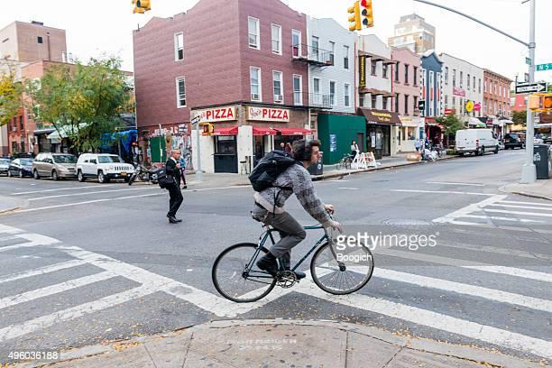 NYC Mann fährt Fahrrad auf der Bedford Avenue, Williamsburg, Brooklyn, USA