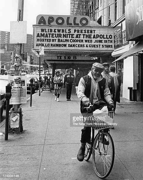 Man rides bike on sidewalk in front of the Apollo theater marquee reads 'WLIB WBLS Present Amateur Nite at the Apollo Hosted by Ralph Cooper Wed June...