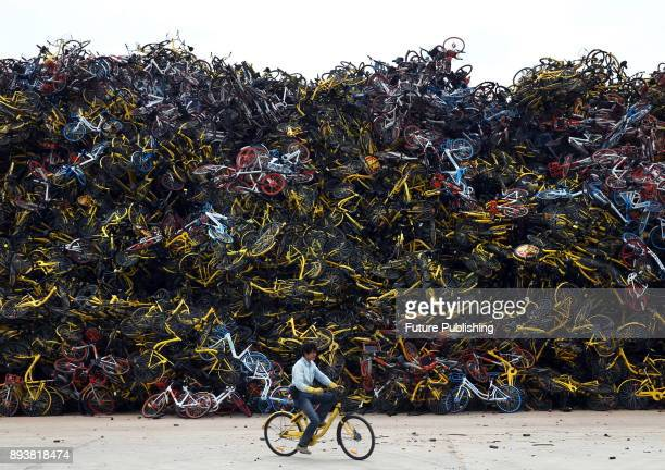 A man rides by a huge pile of rental bikes confiscated by the urban administration authority in Xiamen in southeast China's Fujian province Wednesday...