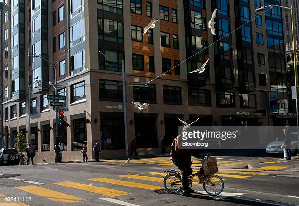 A man rides his bicycle across Golden Gate Street in the Tenderloin district of San Francisco California US on Tuesday Jan 20 2015 In a city where...