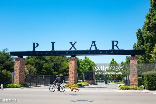A man rides his bicycle and walks his dog past the entry gates at the headquarters of Pixar Animation Studios in downtown Emeryville California with...