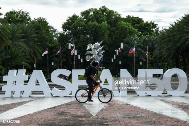 A man rides his bicycle in front of the ASEAN logo near the venue for the Association of Southeast Asia Nations Regional Forum meeting in Manila on...