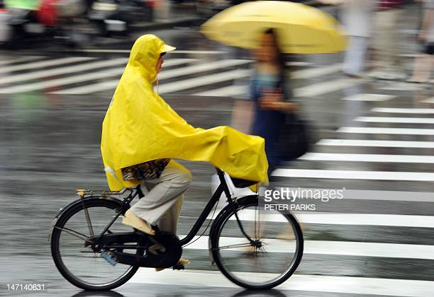 A man rides his bicycle in the rain on a street in Shanghai on June 26 2012 Heavy rain ontinues to fall in many parts of southern and eastern China...