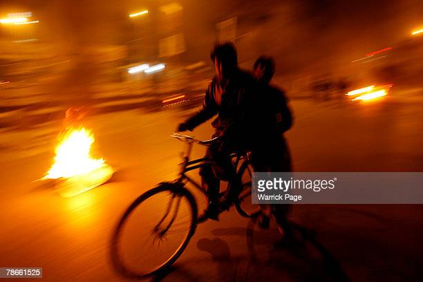 A man rides his bicycle near tyres set alight by rioters enraged by the assassination of former prime minister Benazir Bhutto on December 27...