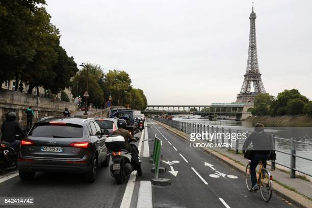 TOPSHOT A man rides his bicycle on the newly created bicycle track past cars stuck in a traffic jam along the Seine River near the Bir Hakeim Bridge...