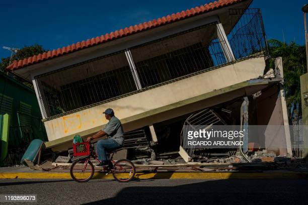 Man rides his bicycle pass by a collapsed house in Guanica, Puerto Rico on January 15 after a powerful earthquake hit the island. - The island is...