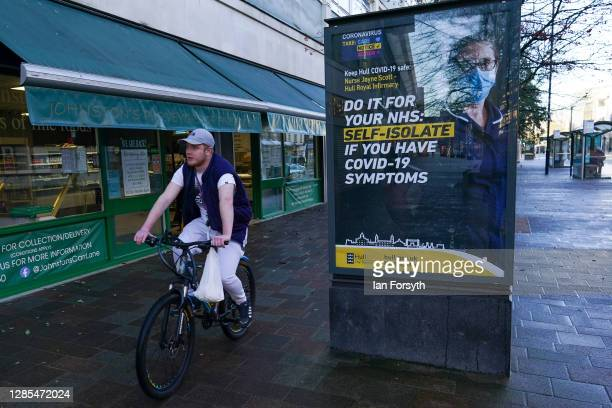Man rides his bicycle past a Covid-19 information board in Hull city centre on November 13, 2020 in Hull, England. Hull recorded 726.8 new cases per...