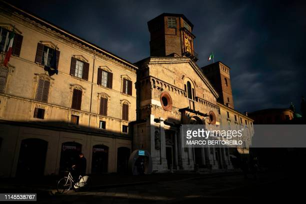 Man rides his bicycle past Duomo of Santa Maria Assunta in Reggio Emilia, on May 15, 2019 Northern Italy. - The Unione Campanari Reggiani is a group...