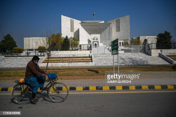 Man rides his bicycle past the Supreme Court building in Islamabad on January 29 where lawyers have filed a last-ditch attempt to overturn the...