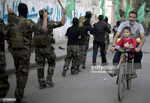 Man rides his bicycle past young members of the Palestinian Islamist movement Hamas during an anti-Israel march on the first anniversary of Israel's...