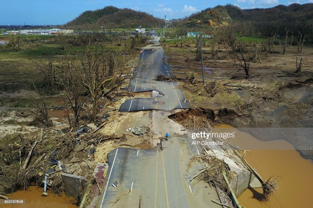 TOPSHOT - A man rides his bicycle through a damaged road in Toa Alta, west of San Juan, Puerto Rico, on September 24, 2017 following the passage of Hurricane Maria. Authorities in Puerto Rico rushed on September 23, 2017 to evacuate people living downriver from a dam said to be in danger of collapsing because of flooding from Hurricane Maria. / AFP PHOTO / Ricardo ARDUENGO