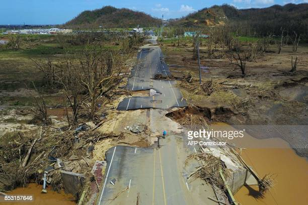Man rides his bicycle through a damaged road in Toa Alta, west of San Juan, Puerto Rico, on September 24, 2017 following the passage of Hurricane...