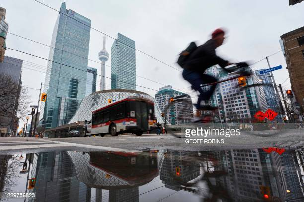 Man rides his bicycle through the relatively quiet streets in Toronto, Ontario on November 23 the first day of a new lockdown in the city. - Canada's...