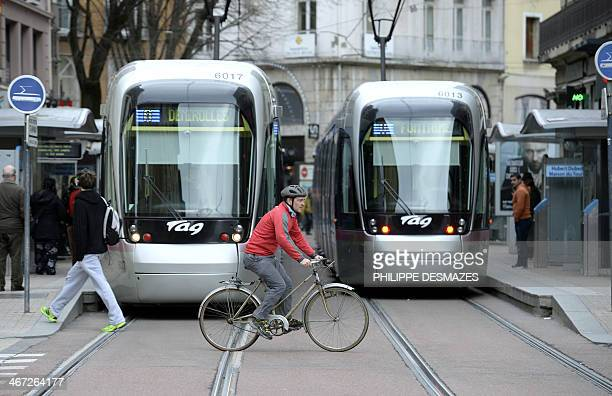 A man rides his bike front of trams in a street of Grenoble on February 6 2014 AFP PHOTO/PHILIPPE DESMAZES