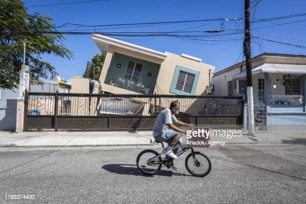 A man rides his bike in front of a collapse house after 64magnitude earthquake hit Guanica Puerto Rico on January 11 2020